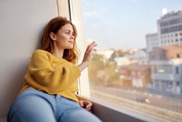 Uma mulher bonita com um suéter amarelo está deitada no parapeito da janela e olha pela janela