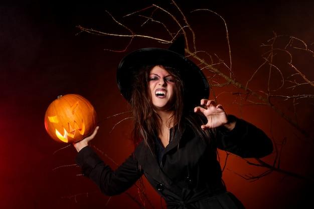 Uma mulher bonita com uma abóbora na mão