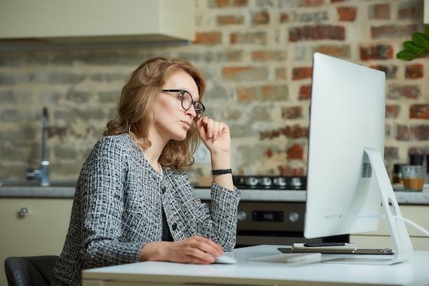 Uma mulher bonita de óculos trabalha remotamente em um computador desktop em seu estúdio. um chefe do sexo feminino à procura de informações em uma videoconferência em casa. uma professora se preparando para uma palestra on-line.