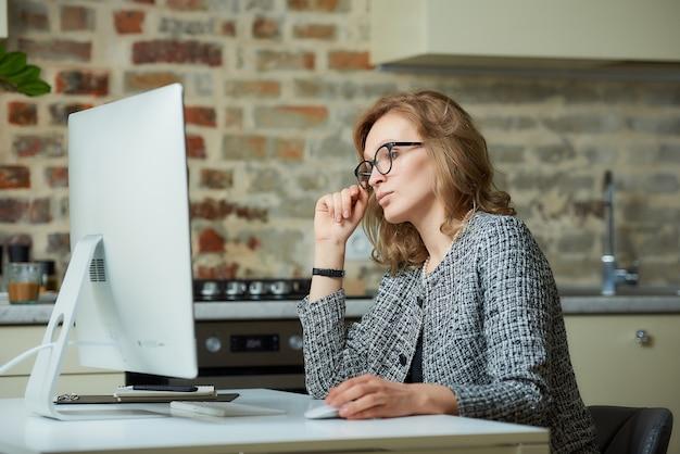 Uma mulher bonita de óculos trabalha remotamente em um computador desktop em seu estúdio. um chefe do sexo feminino à procura de informações em uma videoconferência em casa.