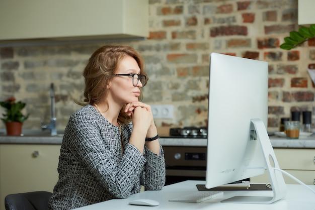 Uma mulher bonita de óculos trabalha remotamente em um computador desktop em seu estúdio. um chefe feminino senta os braços cruzados em uma videoconferência em casa.