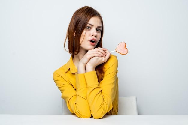 Uma mulher bonita e alegre com um pirulito nas mãos e uma camisa amarela está sentada à mesa