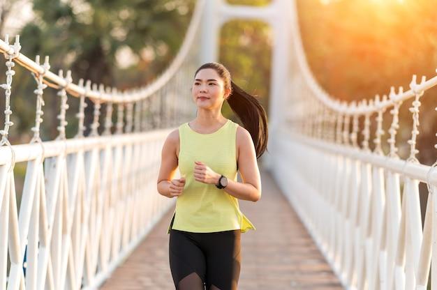 Uma mulher bonita e brilhante correndo em uma ponte de madeira