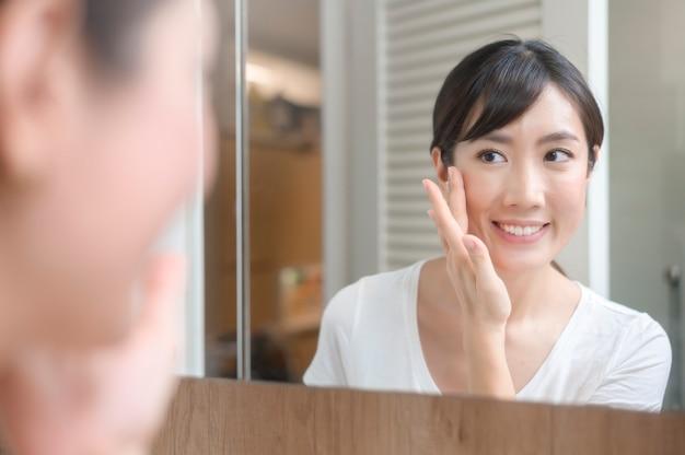 Uma mulher bonita e feliz aplicando creme hidratante no rosto, conceito de cuidados com a pele e tratamento