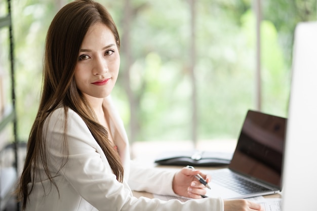 Uma mulher bonita e inteligente está sentado em sua mesa no escritório.