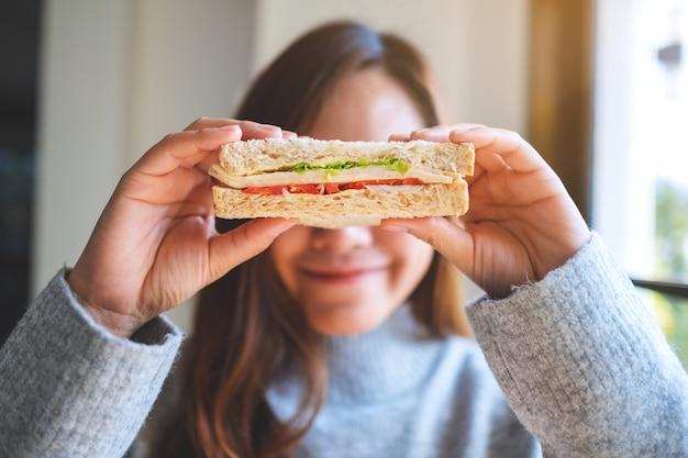 Uma mulher bonita e sorridente segurando um pedaço de sanduíche de trigo integral cobrindo os olhos