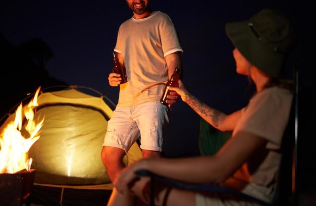 Uma mulher bonita e um homem bonito estão sentados em cadeiras dobráveis perto da tenda perto do fogo, bebendo cerveja e se divertindo à noite na praia à beira-mar.