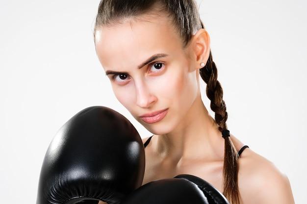 Uma mulher bonita em luvas de boxe olha para a câmera.