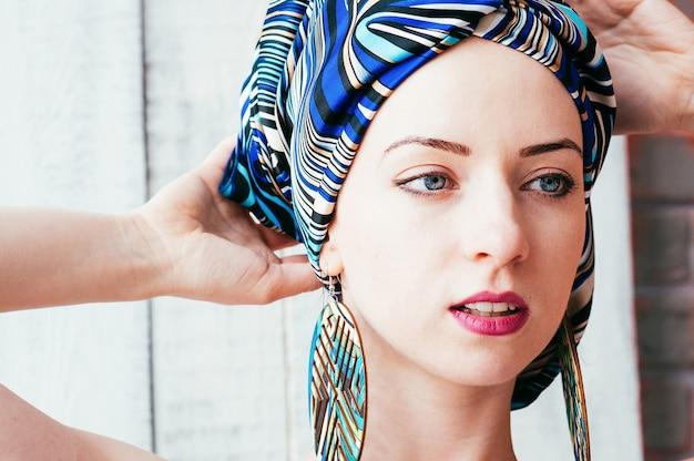 Uma mulher bonita em um lenço azul de uma maneira africana