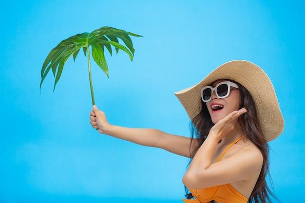 Uma mulher bonita em um maiô segurando uma folha verde coloca no azul