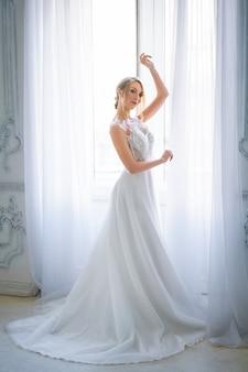 Uma mulher bonita em um vestido de noiva branco com uma bela maquiagem e penteado fica na janela