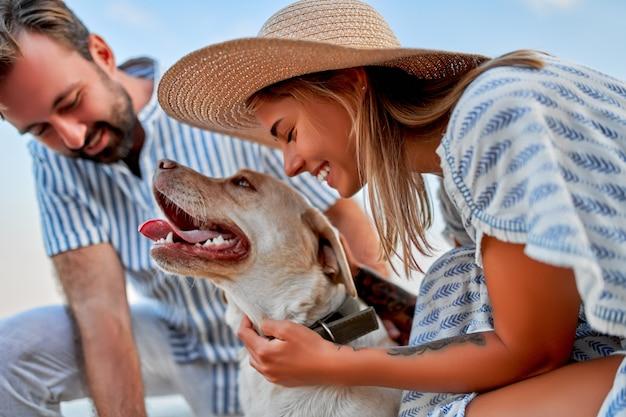 Uma mulher bonita em um vestido e um chapéu de palha e um homem bonito em uma camisa listrada com seu cachorro labrador estão se divertindo à beira-mar.
