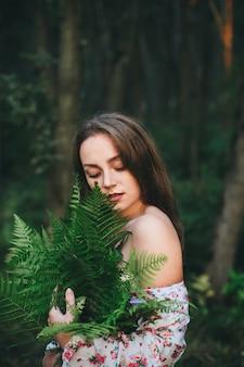 Uma mulher bonita em um vestido floral está sentada com um buquê de samambaia na floresta.