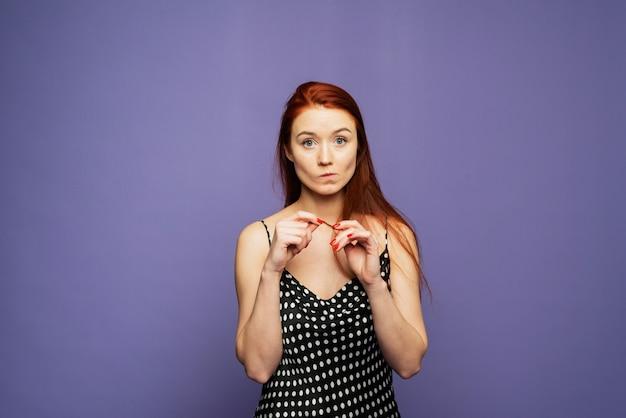 Uma mulher bonita envergonhada e surpresa fica em um fundo lilás. modelo para o seu anúncio e texto. mulher americana franze os lábios, olha com perplexidade
