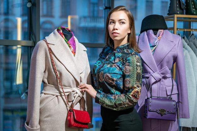 Uma mulher bonita escolhe um casaco na loja