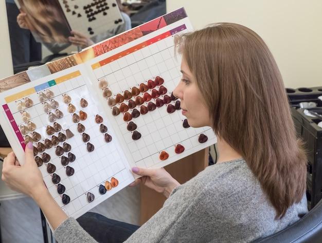 Uma mulher bonita escolhe uma tintura de cabelo. escolhendo uma cor de tinta.