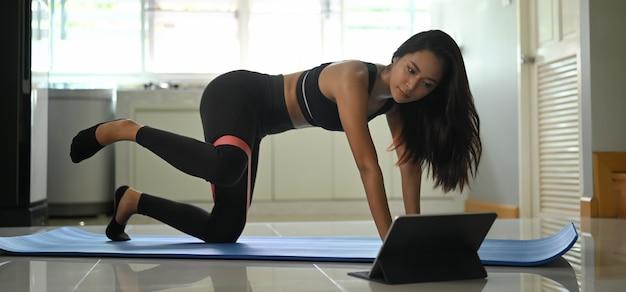 Uma mulher bonita está olhando para um tablet enquanto faz um exercício em uma confortável sala de estar.