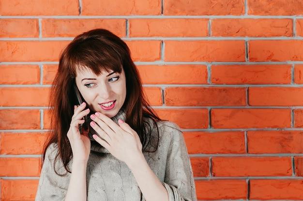 Uma mulher bonita falando pelo celular, sorrindo, parede de tijolos no fundo