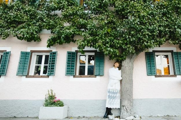 Uma mulher bonita fica ao lado da árvore, sorrindo e curtindo a vida