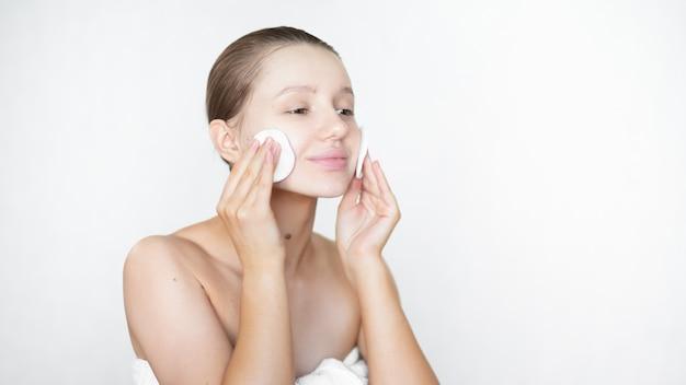 Uma mulher bonita limpa a pele com um toner facial usando uma almofada de algodão e sorri