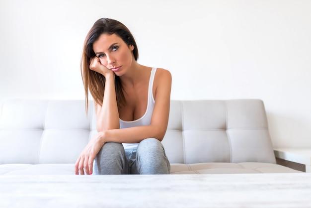 Uma mulher bonita mas triste em casa no sofá