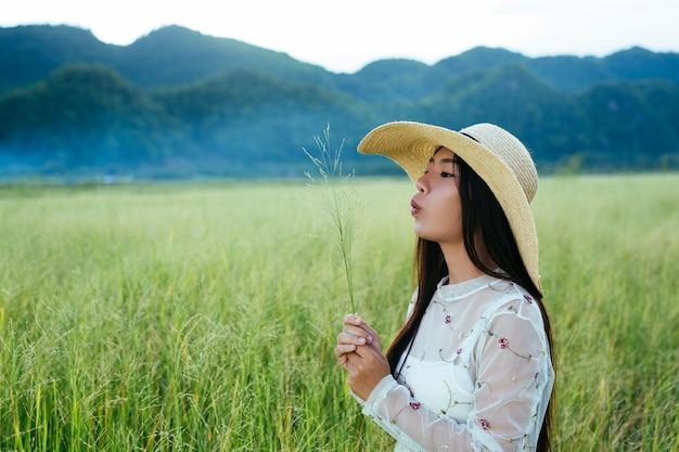 Uma mulher bonita que está feliz no prado com uma grande montanha como um.
