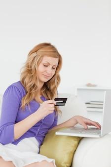 Uma mulher bonita que está sentada em um sofá vai fazer um pagamento na internet