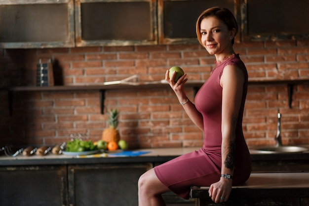 Uma mulher bonita que senta-se na mesa de cozinha, prende a maçã.