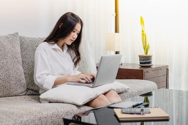 Uma mulher bonita que trabalha em casa com um laptop e tablet.
