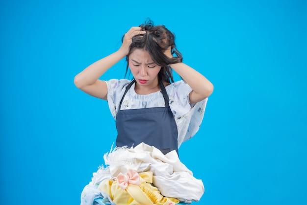 Uma mulher bonita, segurando um pano preparado para lavar em azul