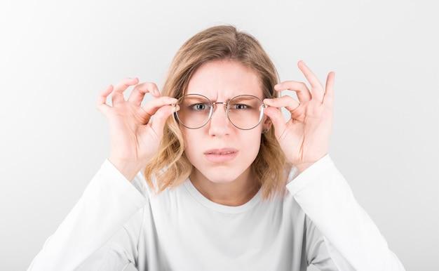 Uma mulher bonita tem longos cabelos loiros e óculos elegantes, olha para a frente com uma expressão pensativa