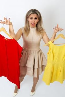Uma mulher bonita tem uma escolha difícil, que vestido escolher vermelho ou amarelo?