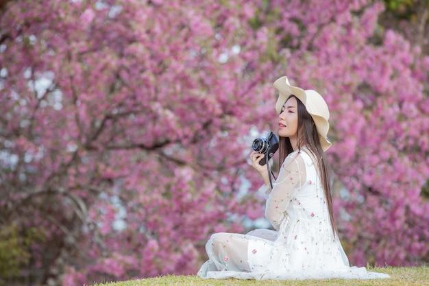 Uma mulher bonita tira uma foto com uma câmera de filme no jardim de flores de sakura.