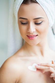 Uma mulher bonita usando um produto de cuidados da pele, hidratante ou loção e skincare cuidando de sua pele seca. creme hidratante nas mãos femininas