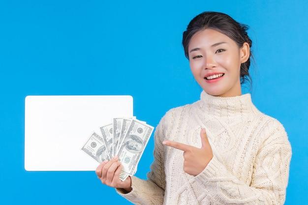 Uma mulher bonita vestindo um novo tapete branco de mangas compridas, segurando uma placa branca e uma nota de dólar em um azul. negociação.
