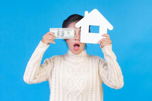 Uma mulher bonita vestindo um tapete branco de mangas compridas novo que mantém o símbolo da casa e notas de dólar em um azul. negociação.