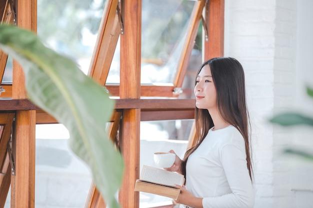 Uma mulher bonita, vestindo uma camisa branca de mangas compridas, sentado em uma cafeteria