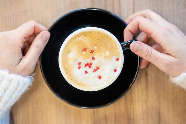 Uma mulher branca segura uma caneca de café preta em uma cafeteria ou em casa, um americano quente delicioso e aromático ou um café expresso