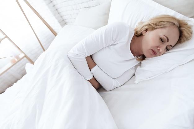 Uma mulher branca tem uma dor de estômago deitada na cama.