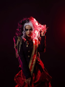 Uma mulher brilhante e chocante com um penteado preto e branco está vestida com um uniforme decorado e uma saia rodada. retroiluminação vermelha na parte de trás. dançando em um fundo preto
