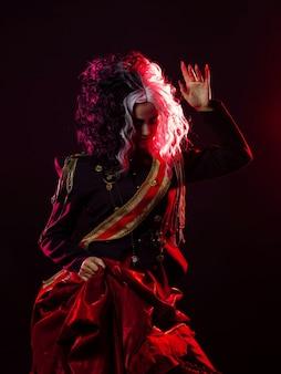 Uma mulher brilhante e chocante com um penteado preto e branco está vestida com um uniforme decorado e uma saia rodada. retroiluminação vermelha na parte de trás.