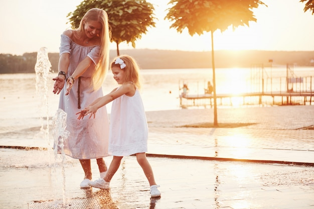Uma mulher brincando com uma criança perto do mar no parque ao pôr do sol