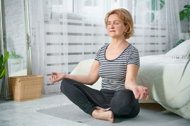 Uma mulher calma mais velha medita na posição de lótus em casa