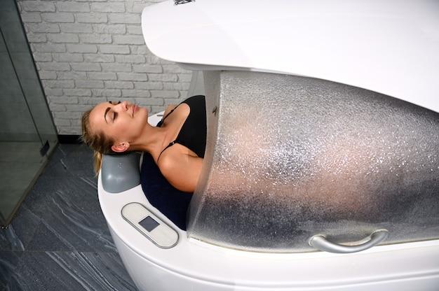 Uma mulher calma que desfruta de hidromassagem, vibromassagem e tratamento anticelulite durante procedimentos estéticos com equipamentos modernos - uma cápsula de spa no centro de bem-estar.