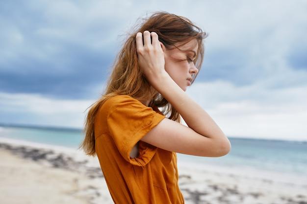 Uma mulher caminha ao longo da praia