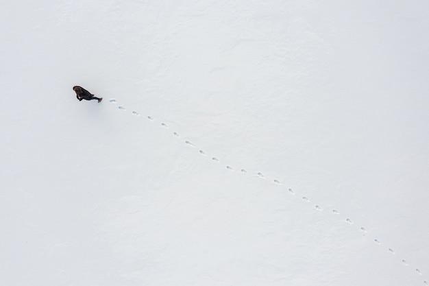 Uma mulher caminha pela neve fresca deixando pegadas