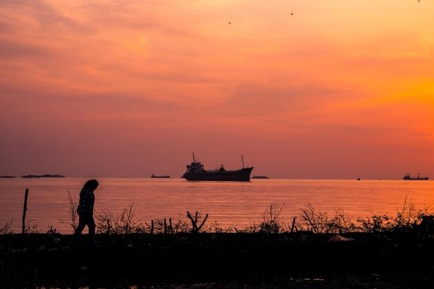 Uma mulher caminhando na costa do mar com um navio na água ao nascer do sol
