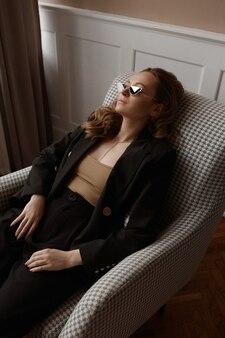 Uma mulher cansada sem maquiagem, usando óculos escuros da moda, descansa em uma poltrona