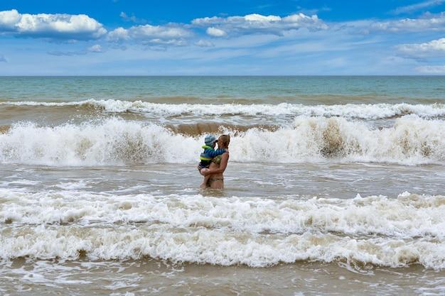 Uma mulher carrega nos braços uma criança de um mar tempestuoso. resgatar uma criança em uma tempestade