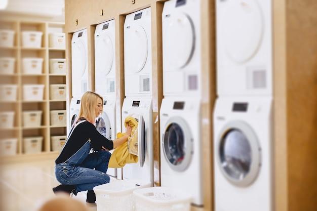 Uma mulher carregar os lençóis na lavanderia para lavar e secar